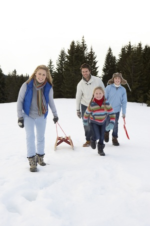 Young Family Walking Through Snow With Sled photo