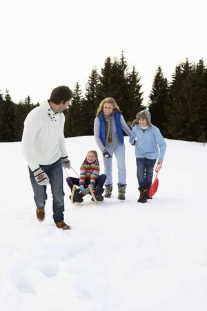 Young Family In Alpine Snow Scene With Sled photo