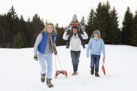 dragging: Young Family Walking Through Snow With Sled Stock Photo
