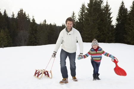 dragging: Young Father And Daughter Walking In Snow With Sleds