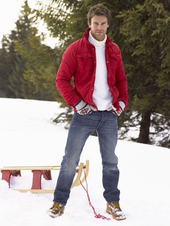 Young Man With Sled In Alpine Snow Scene Stock Photo - 11246898