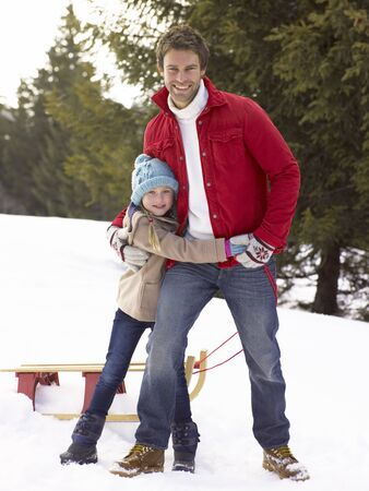 sledging people: Young Father And Daughter In Snow With Sled Stock Photo