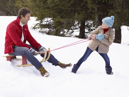 dragging: Young Girl Pulling Father Through Snow On Sled Stock Photo