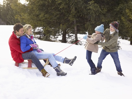 dragging: Young Girl And Boy Pulling Parents Through Snow On Sled