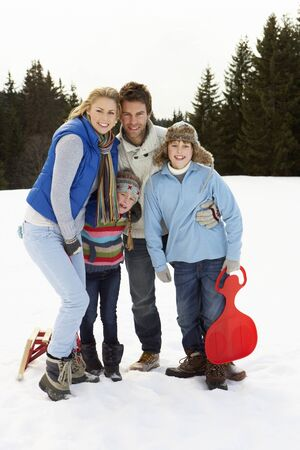 Young Family In Alpine Snow Scene With Sleds photo