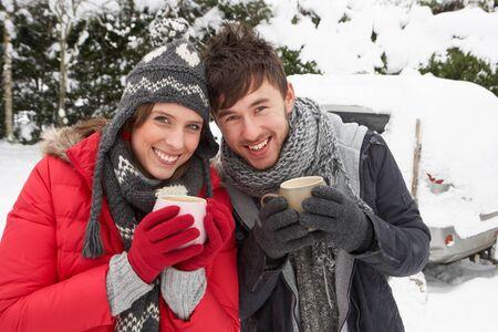 ropa invierno: Pareja joven en la nieve con el coche
