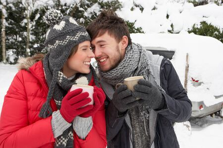 warm drink: Young couple in snow with car