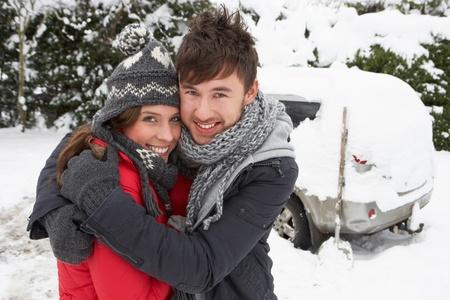 Jeune couple dans la neige avec une voiture