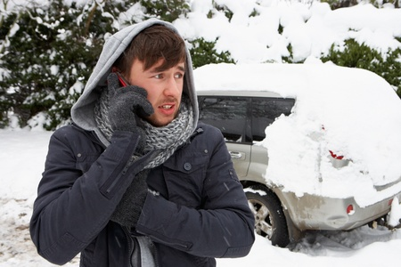 Young man in snow with broken down car photo