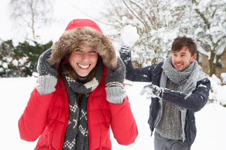 warmly: Young couple having snowball fight