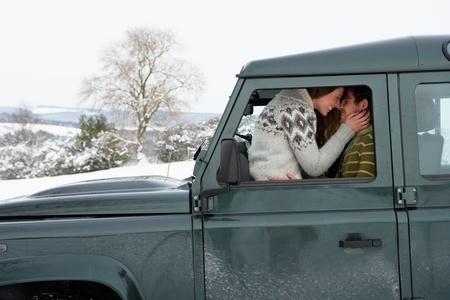 enamorados besandose: Pareja joven en el coche en la nieve