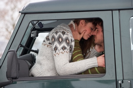 warmly: Young couple in car in snow