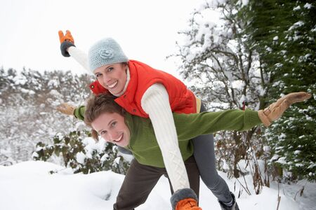 Young couple having fun in snow photo