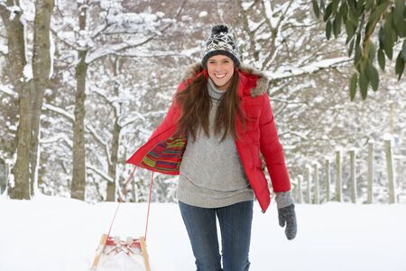 warmly: Young woman in snow with sledge Stock Photo