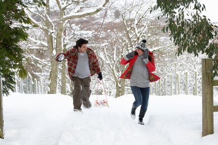sledding: Young couple having snowball fight