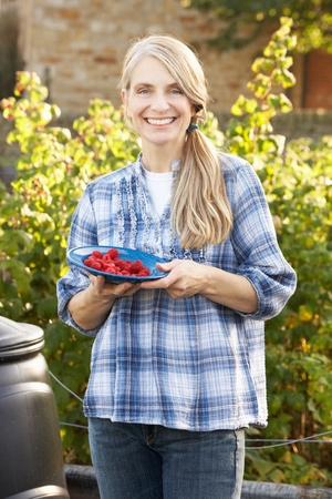 mid age: Woman with home-grown fruit