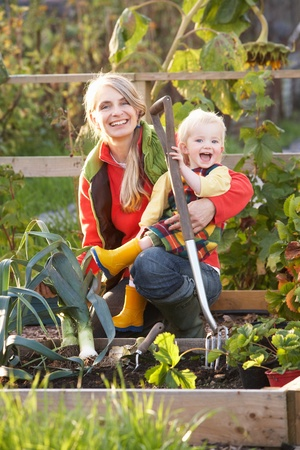 leeks: Woman working on allotment with child Stock Photo