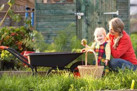 plots: Woman working on allotment with child Stock Photo