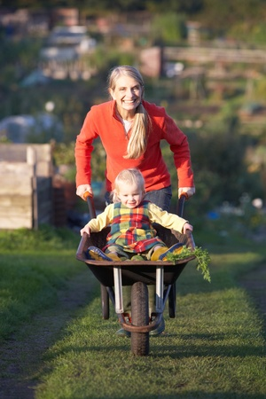 plot: Woman working on allotment with child Stock Photo