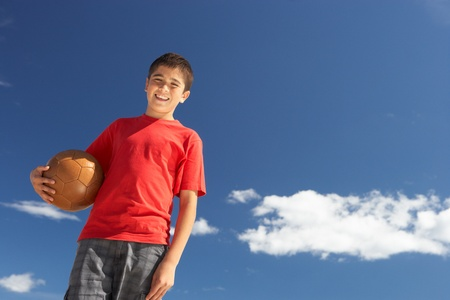 Teenage boy holding football photo