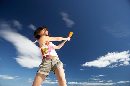 Teenage girl playing baseball on beach photo