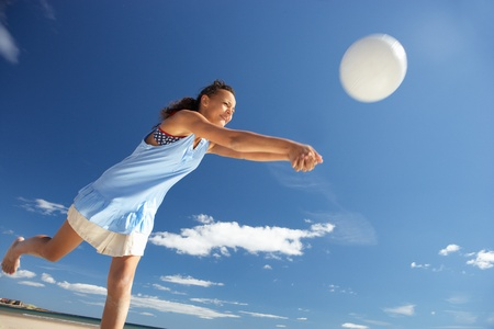 Teenage girl playing beach volleyball photo