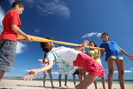 Teenagers doing limbo dance on beach photo