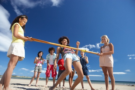 Teenagers doing limbo dance on beach Stock Photo - 11246735