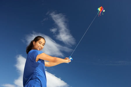flying kites: Teenage girl flying a kite