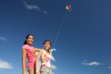 string together: Teenage girls flying a kite