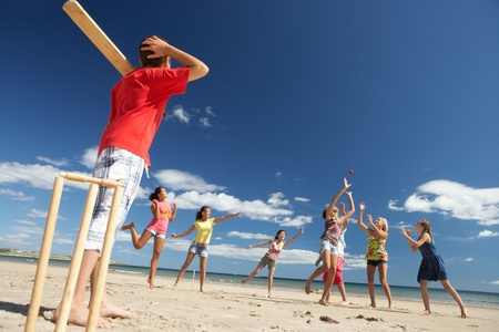 cricket ball: Teenagers playing cricket on beach Stock Photo