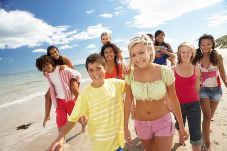 mixed race teen: Teenagers walking on beach