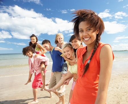 multiracial group: Adolescentes caminando en la playa