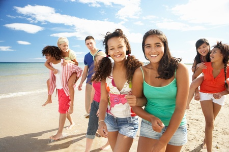 teenage girls: Teenagers walking on beach