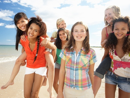 piggyback: Teenage girls walking on beach Stock Photo