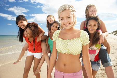 multiracial groups: Teenage girls walking on beach Stock Photo