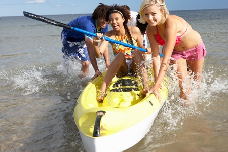 piragua: Adolescentes en el mar con una canoa Foto de archivo