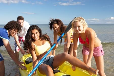 piragua: Los adolescentes en el mar con una canoa