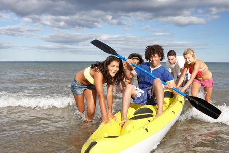 Teenagers in sea with canoe photo
