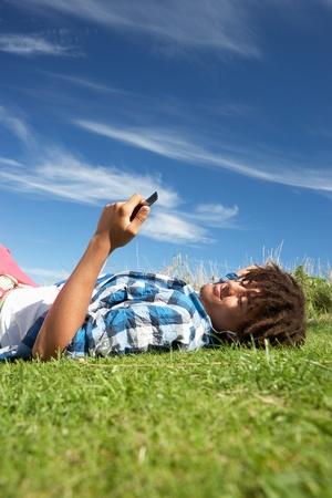 Teenage boy lying on grass with phone Stockfoto