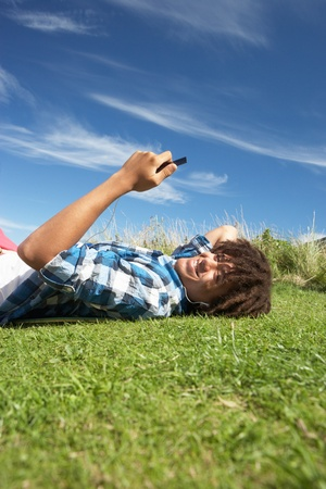 Teenage boy lying on grass with phone photo