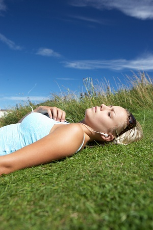 Teenage girl lying on grass with mp3 player Stock Photo - 11246656