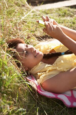 Teenage girl lying on grass with phone photo