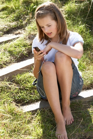 young girl barefoot: Teenage girl using mp3 player outdoors Stock Photo
