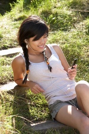 earphone: Teenage girl using mp3 player outdoors Stock Photo