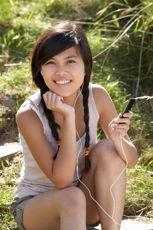 barefoot teens: Teenage girl using mp3 player outdoors Stock Photo