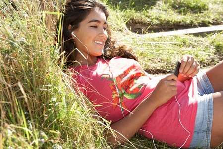 Teenage girl using mp3 player outdoors photo