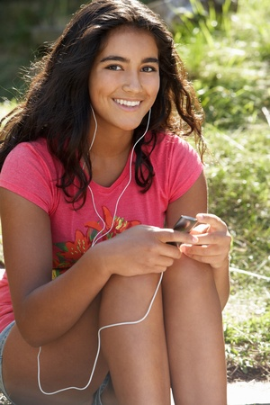 Teenage girl using mp3 player outdoors Stock Photo