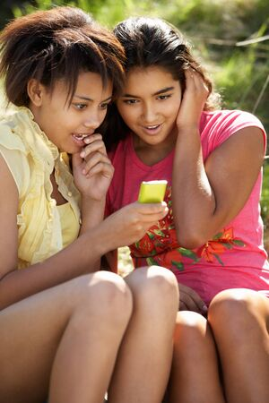 Teenage girls using phone outdoors photo