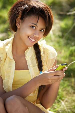 Teenage girl using phone outdoors photo
